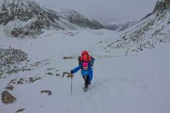 Alpiniste féminin avec le sac à dos, le casque et le harnais avec s'élever en montagne images stock