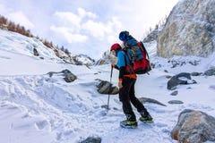 Alpiniste féminin avec le sac à dos, le casque et le harnais avec s'élever en montagne photographie stock libre de droits