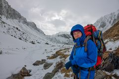 Alpiniste féminin avec le sac à dos, le casque et le harnais avec s'élever en montagne photos stock