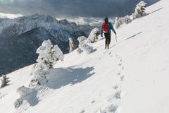 Alpiniste marchant sur la pente neigeuse Photo stock