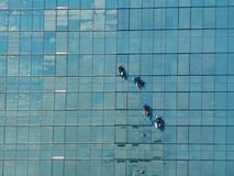 Alpiniste quatre s'élevant pour nettoyer le verre de fenêtre de construction Photographie stock