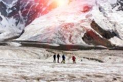 Alpinisti che camminano attraverso il grande ghiacciaio Immagine Stock