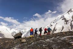 Alpinisti che camminano attraverso il grande ghiacciaio Immagini Stock