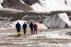 Alpinisti che camminano attraverso il grande ghiacciaio Fotografie Stock
