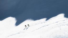 Alpinisti dello sci nelle ombre delle montagne Immagine Stock