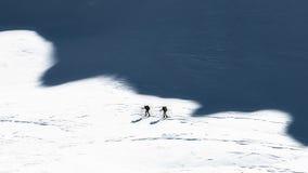 Alpinisti dello sci nelle ombre delle montagne Stile artistico Fotografia Stock