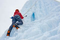 Alpinistkvinnan med is bearbetar yxan i orange hjälm som klättrar ett l royaltyfria foton