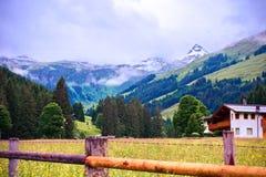 Alpint berg med ett snöig maximum med ett wood staket och chalet i förgrunden på Talschluï ¿ ½ i Saalbach, Österrike arkivbild