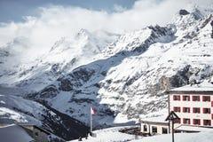 Alpint hus i höga berg som täckas av moln royaltyfria foton
