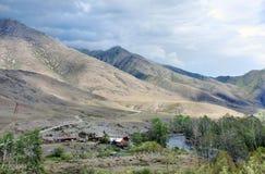 Alpint landskap med en flod och en bikupa på lutningen av berg Arkivfoto