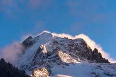 Alpint maximum i vinter med stormmoln som bakom bygger Arkivfoton