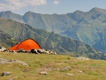 Alpint tält i överkanten av bergen Arkivfoto