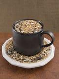 Alpiste en una taza y un platillo marrones Fotografía de archivo libre de regalías