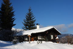 In The Alps. Traditional house in the snowy winter landscape of the Alps Stock Photo