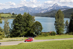 Alps, car speeding od village road Royalty Free Stock Images