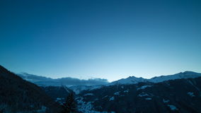 Alps day to night timelapse. Day to night timelapse, the sun setting down behind mountains and transition into a starry night sky over the Val d'Anniviers, a stock video