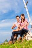 Alps - Hiking Couple takes break in mountains Stock Photo