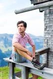Alps - mężczyzna siedzi przy kabiną w Tirol na górach Obraz Stock