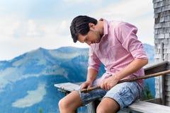 Alps - mężczyzna siedzi przy kabiną w Tirol na górach Obrazy Stock