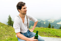 Alps - Man in mountains drinking beer from bottle Stock Photos