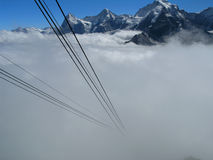Alps with mist and cable car. Cables from cable car descending into fog with Alps in background Royalty Free Stock Photos