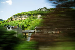 Alps mountains and hidden house seen from fast train in motion Royalty Free Stock Photography