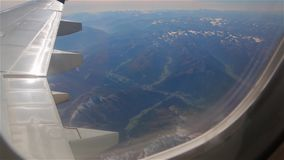Alps from the plane. Alps mountains from the plane panoramic view through the airplane wing flying over Austria stock video