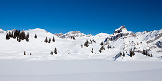 The Alps. Panoramic photo of snow covered mountains on a bight day with deep blue sky in the Swiss Alps royalty free stock images