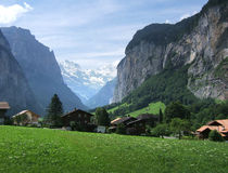 Alps Scene. View of a meadow and chalets in Switzerland surrounded by mountains stock photography