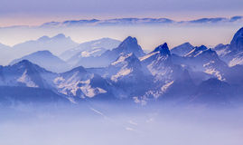 Alps. Snow covered mountains and rocky peaks in the Swiss Alps, over blue sky Royalty Free Stock Photography