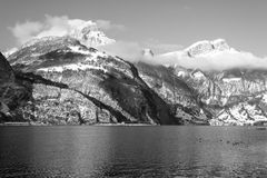 Alps in Switzerland. Journey to Christmas. Winter landscape. Mountain range in the clouds. On the tops of snow drifts. Lake and birds. Black and white Stock Images