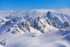 Alps in Switzerland in wintertime. Wintertime view from Mt. Titlis in Switzerland. The Titlis is a mountain, located on the border between the Swiss cantons of Stock Photos