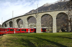 Alps Train glides to viaduct Stock Photo