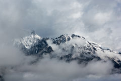 The Alps. View of the snowcapped Alps with clouds Royalty Free Stock Photography