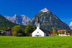 Alps village with cathedral Stock Image