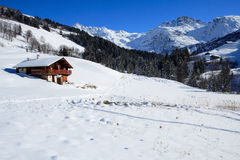 Alps winter holiday. Alpine view of a chalet in the winter snow with bright blue sky Stock Image