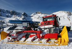 Alps winter view with ratrak. A colorful ratrak or snowcat in the view of winter Alps peaks in the sun Stock Photo