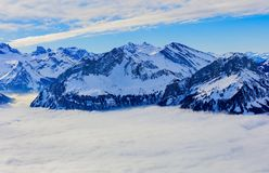 The Alps, wintertime view from Mt. Fronalpstock. Summits of the Alps rising from sea of fog - a wintertime view from Fronalpstock mountain in the Swiss canton of Stock Images