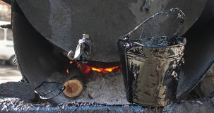 Alquitrán de ebullición en el barril de acero sucio que se coloca en el fuego 4K almacen de video