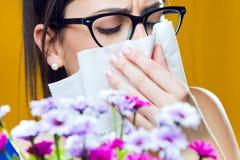 Alérgico a la chica joven del polen con un ramo de flores Foto de archivo