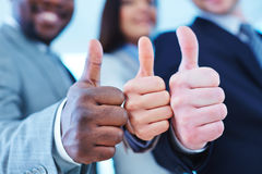 Alright. Thumb up gesture shown by group of employees stock photo
