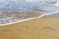 2015, als das neue Jahr, geschrieben auf den Sand eines Strandes Stockbilder