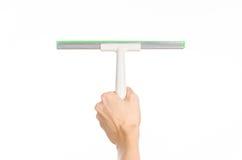 Als thema hebben de huishouden schoonmakende en wassende vensters: man hand die een groene die schrapervensters houden op een wit Stock Afbeelding