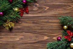 Als thema hebben de nieuwjaren Vooravond en Kerstmis met het klatergoud van de pijnboomboom op de lege houten achtergrond voor uw stock fotografie