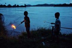 als voorbereiding op een godsdienstige viering twee steekt de jonge jongen omhoog de kaarsen rond het theravada boeddhistische kl royalty-vrije stock afbeelding