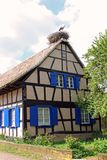 Alsatian frame house with a stork`s nest on the roof stock photography