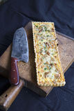 Alsatian Onion Tart with knife on wooden cutting board Royalty Free Stock Images