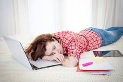 Alseep dai capelli rossi dello studente sul computer portatile mentre studing Immagine Stock