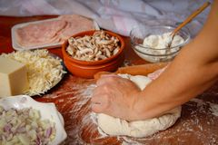 Women`s hands knead the dough for pizza on wooden table stock image