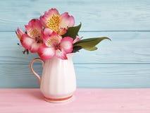 Alstroemeria de la primavera de la flor del florero estacional en un arreglo de madera fotografía de archivo